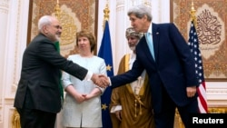 U.S. Secretary of State John Kerry (R) and Iranian Foreign Minister Javad Zarif (L) shake hands as Omani Foreign Minister Yussef bin Alawi (2nd R) and EU envoy Catherine Ashton watch in Muscat, Oman, Nov. 9, 2014.