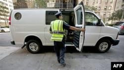 Một nhân viên cảnh sát New York xem xét một chiếc xe trên đường số 59 và Park Avenue ở Manhattan