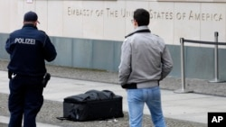 Police officers photograph a suitcase in front of the US embassy in Berlin, Germany, March 11, 2016.