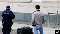 Agentes da polícia fotografam a mala no exterior da embaixada