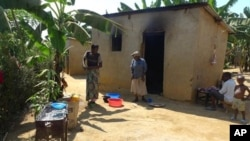 Residents cook food behind their homes in the Reconciliation Village