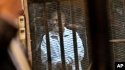 被罷免的埃及總統穆爾西在2014年1月18日的庭審中站在玻璃籠裡(資料照片)