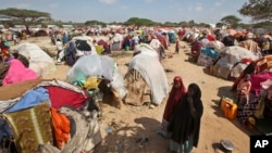 Drought-stricken Somalis walk through a camp in the Garasbaley area on the outskirts of Mogadishu, Somalia, March 28, 2017.