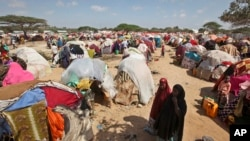 Newly displaced Somalis walk through a camp in the Garasbaley area on the outskirts of Mogadishu, Somalia, March 28, 2017.