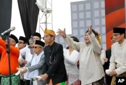 Presiden Joko Widodo (kiri) dan Ma'ruf Amin (kiri) dan capres-cawapres paslon 02, Prabowo Subianto-Sandiaga Uno (kanan) melepas merpati dalam upacara menandai dimulainya kampanye pemilu, 23 September 2018. (Foto: AP/Tatan Syuflana)
