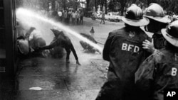 FILE - In this July 15, 1963 file photo, firefighters aim their hoses on civil rights demonstrators in Birmingham, Ala.