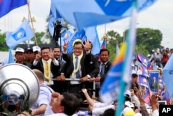 FILE: Sam Rainsy, center, president of Cambodia National Rescue Party (CNRP) greets his supporters together with his party's Vice President Kem Sokha, on Rainsy's left, on his arrival at Phnom Penh International Airport in Phnom Penh, Cambodia, Friday, July 19, 2013.