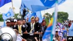 Ông Sam Rainsy (giữa), chủ tịch Đảng Cứu Quốc Campuchia chào các ủng hộ viên khi về đến sân bay Phnom Penh, 19/7/13