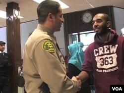 Sherif Morsi, Wakil Sheriff di Los Angeles yang juga seorang Muslim ini, beramah-tamah dengan seorang jemaah sebuah masjid di LA.
