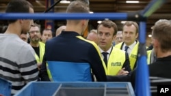 French President Emmanuel Macron, center right, talks with Whirlpool employees during a visit of the Whirlpool factory in Amiens, Oct. 3, 2017.