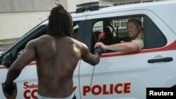 Seorang warga kulit hitam AS memberikan bunga mawar kepada polisi di Ferguson, Missouri (19/8).