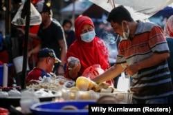 Seorang perempuan mengenakan masker untuk mencegah penularan COVID-19 sedang berbelanja di sebuah pasar tradisional di Jakarta, 1 Maret 2021. (Foto: Willy Kurniawan/Reuters)