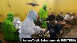Petugas medis yang mengenakan alat pelindung mengambil sampel darah dari pengunjung yang dites virus corona di Surabaya, provinsi Jawa Timur, 18 April 2020. (Foto: Antara/Didik Suhartono) via Reuters)