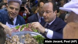 French President Francois Hollande is offered pieces of meat, during his visit to the agricultural fair in Paris, Saturday, Feb. 22, 2014. (AP Photo/Alain Jocard, Pool)