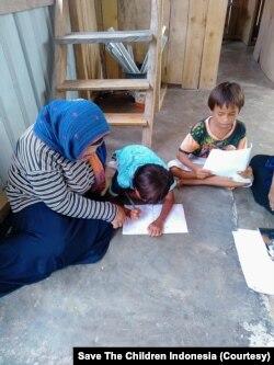 Dua orang anak yang sedang belajar dibimbing oleh guru yang mendatangi rumah mereka di desa Lende Tovea, Kecamatan Sirenja, Donggala, Sulawesi Tengah. (Foto: Save The Children Indonesia)