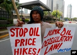 Protesters, mostly public transport drivers, display placards as they picket Petron Oil, the country's largest oil company, to protest the almost-weekly price increase of oil and other products and to demand its total rollback, June 5, 2018 in suburban Manila.