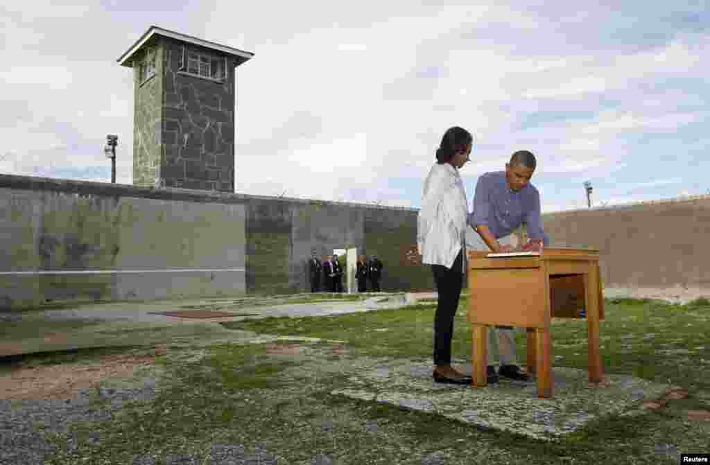 U.S. President Barack Obama writes in a guest book as he tours Robben Island with first lady Michelle Obama, near Cape Town, June 30, 2013.
