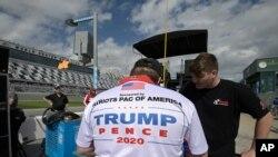 Un miembro del equipo de Joe Nemechek, con un logotipo del patrocinador que apoya al presidente Donald Trump, en su puesto de parada en la pista antes de una carrera de la serie NASCAR Xfinity en el Daytona International Speedway, el sábado 15 de febrero de 2020, en Daytona Beach, Florida.