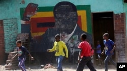 FILE: Children play soccer next to a defaced portrait of Former Zimbabwean President Robert Mugabe in Harare, Friday, Sept, 6 2019.