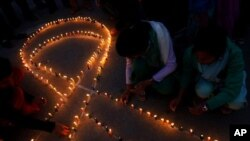 Nepalese people light candles in the shape of the red ribbon, the universal symbol of awareness and support for those living with HIV, in Katmandu, Nepal, Wednesday Nov. 30, 2011. (AP Photo/Niranajan Shrestha)