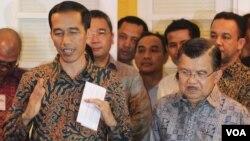 Presiden dan Wakil Presiden terpilih, Joko Widodo (kiri) dan Jusuf Kalla, saat mengumumkan postur kabinet di rumah Transisi di Menteng, Jakarta hari Senin 15/9 (foto: VOA/Fathiyah).