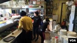 Pengungsi dari Bhutan mempersiapkan makanan Nepal di Café Momo di Manchester, New Hampshire (6/2). (VOA/A. Pande)