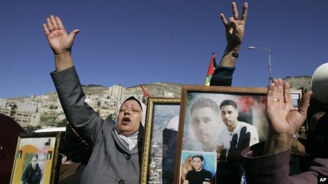 Phụ nữ Palestine cầm hình ảnh các tù nhân bị giam giữ tại Israel trong một cuộc biểu tình tại thành phố Nablus, ngày 4/2/2013.