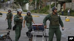 National Guard soldiers carry a stretcher outside of El Rodeo I prison during a riot inside the jail in Guatire, Venezuela, June 17, 2011