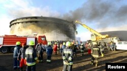Firefighters work to put out a fire at a storage oil tank in the port of Es Sider, Jan. 2, 2015.
