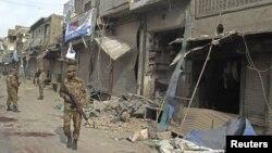 Служба безопасности патрулирует место взрыва в Дера Исмаил Хан, Пакистан. 25 ноября 2012 года