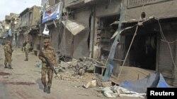 Pasukan keamanan Pakistan memeriksa lokasi ledakan di dekat prosesi kaum Syiah di Dera Ismail Khan hari Minggu (25/11).