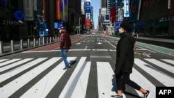 戴着口罩的行人走过纽约市时报广场。(2020年3月22日)