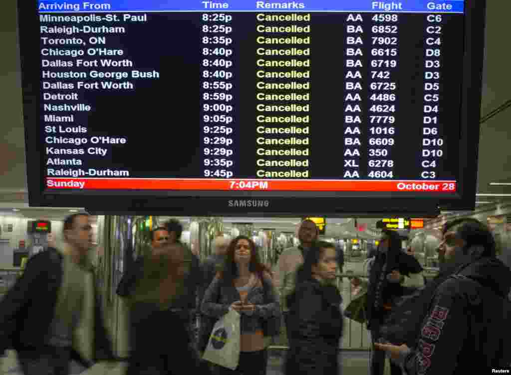 Travelers surround a flight monitor showing cancelled flights at LaGuardia airport in New York October 28, 2012.