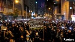 香港示威者星期天(12月8日)在人權日大遊行中下打開手機電筒。