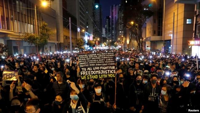 香港示威者星期天(12月8日)在人权日大游行中下打开手机电筒。