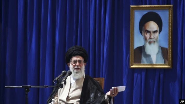 Iranian supreme leader Ayatollah Ali Khamenei delivers a speech, during a ceremony marking the 23rd death anniversary of the late revolutionary founder Ayatollah Khomeini, shown in the poster at right, at his mausoleum, just outside Tehran, Iran, June 3,