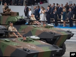 FILE - Tanks parade past President Donald Trump, first lady Melania Trump, French President Emmanuel Macron and his wife Brigitte Macron, during Bastille Day parade on the Champs Elysees avenue in Paris, Friday, July 14, 2017. (AP Photo/Carolyn Kaster)