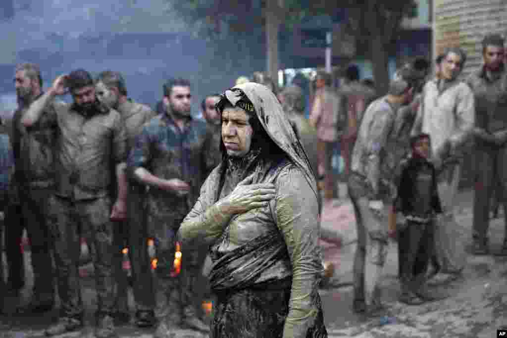 Iranian Shi'ite Muslims mourn after covering themselves with mud during Ashoura rituals, in Khorramabad. Shi'ites mark Ashoura, the 10th day of the Muslim month of Muharram, to commemorate the martyrdom of Imam Hussein, a grandson of Prophet Muhammad and one of Shiite Islam's most beloved saints, during the 7th century Battle of Karbala in present-day Iraq.