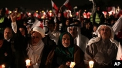 Bahraini opposition leaders Hamza al-Dairi, second left raising his fist, and Jalal Fairooz, right, holding a candle and Bahraini flag, both former opposition lawmakers from al-Wefaq society, participate in a rally in the eastern village of Sitra, Januar