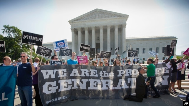 Demonstrators stand on the steps outside the Supreme Court in Washington, June 30, 2014.