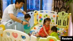 "FILE - Tony Jiang poses with his three children at his house in Shanghai September 16, 2013. In December 2010, Jiang, a Shanghai businessman and his wife welcomed a daughter, born in California to an American surrogate he calls ""my Amanda""."