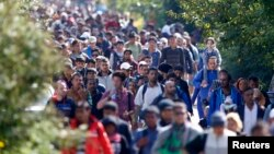 FILE - Migrants walk toward the Austrian border from Hegyeshalom, Hungary, Sept. 23, 2015. Slovakia has fiercely resisted EU efforts to cope with a big influx of mainly Muslim migrants into Europe since 2015.