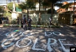 "FILE - Police stand guard outside the residence of Brazil's Vice President Michel Temer where demonstrators wrote the words in Portuguese ""Coup headquarters"" on the street in Sao Paulo, Brazil, April 21, 2016."