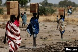 FILE - Women carry boxes of nutritional food delivered by the United Nations World Food Program, in Rubkuai, South Sudan, Feb. 16, 2017.