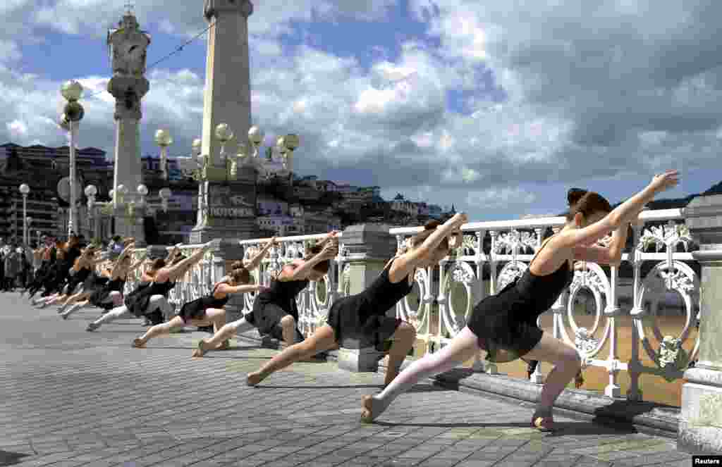 Ballet dancers perform an outside routine, as part of the Month of Dance in San Sebastian, in front of Concha Bay, Spain.
