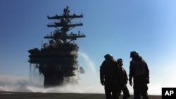 FILE - U.S. Navy deck crew stand near the island on the deck sprayed for radioactive decontamination aboard USS Ronald Reagan off the Japanese coast.