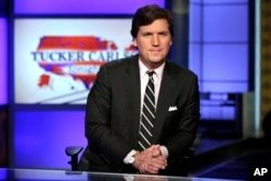 "FILE - Tucker Carlson, host of ""Tucker Carlson Tonight,"" poses for photos in a Fox News Channel studio, in New York, March 2, 2017."