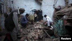 아프가니스탄 페샤와르에 발생한 강진으로 피해를 입은 주민들이 26일 무너진 집터에서 소지품을 찾고 있다.