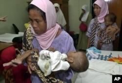 Para ibu menggendong anaknya yang menderita gizi buruk di sebuah klinik di Bogor, Jawa Barat. (Foto: AP)