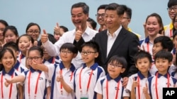 China's President Xi Jinping (center right) and Hong Kong's Chief Executive Leung Chun-ying (center left) give thumbs up as they pose for photographs with members of the Hong Kong Police Force's Junior Police Scheme during a visit to a youth camp in Hong Kong, June 30, 2017.